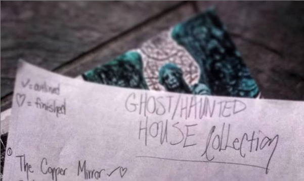 "A blurred image of a sheet of paper on top of a magazine with a oxidized angel statue. The sheet of paper reads ""Ghost/Haunted House Collection 1. The Copper Mirror"""