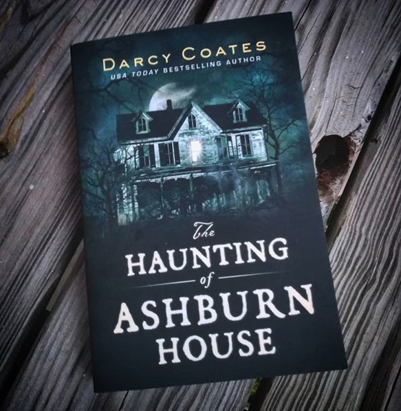 Image of a book with a dark blue and black cover. On the cover is a old house with one window lit. The text on the book reads 'Darcy Coates The Haunting of Ashburn House'